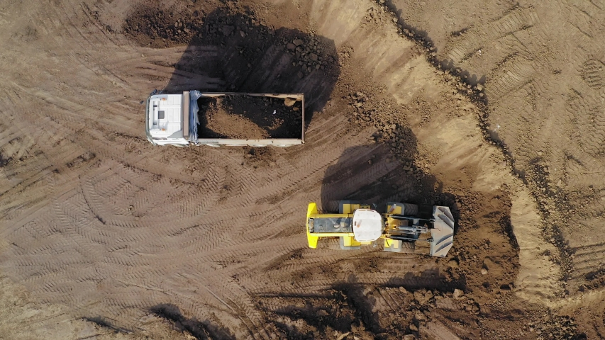 Excavation site with an on going operation of Excavator loading soil onto a Truck, Aerial view. | Shutterstock HD Video #1042904743