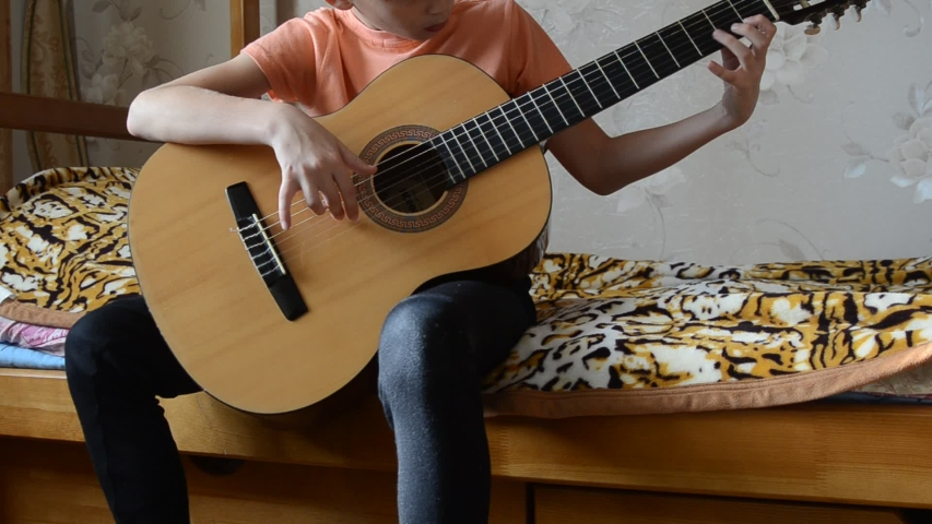 A schoolboy sits on a bed and plays the guitar | Shutterstock HD Video #1042933003