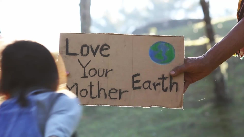 """Hands holding """"Love your Mother Earth"""" Poster on a demonstration due to climate change by plastic pollution. People standing in the park with a sign to save the world. #1042972873"""