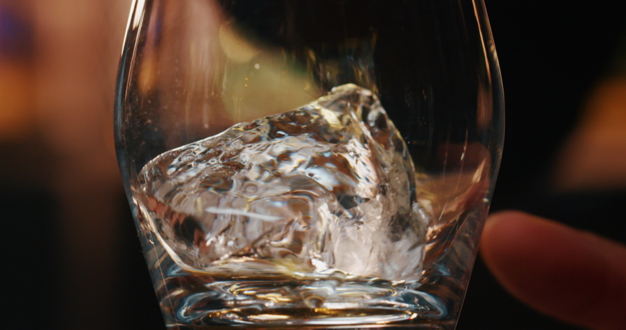 Macro of a professional bartender is putting professional crystal ice cubes in a glass while preparing an alcoholic cocktail to customers at the bar or disco club. | Shutterstock HD Video #1043008543