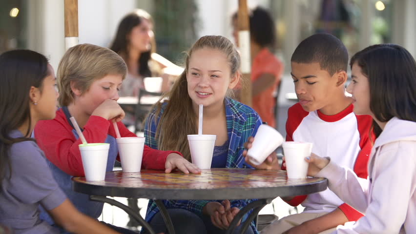 Group of teenage children sitting at table in outdoor caf\x8E and talking.Shot on Sony FS700 at frame rate of 25fps