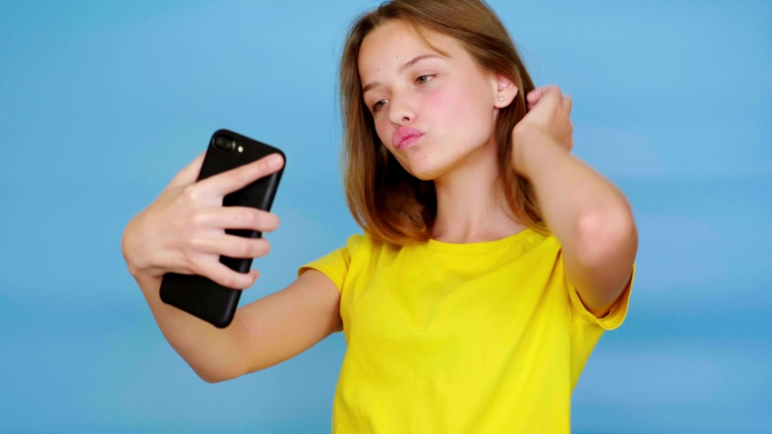 Happy teen girl in a yellow t-shirt is makes a selfie or video on a smartphone and smiling. Blue background with copy space. Teenager emotions. 4k footage | Shutterstock HD Video #1043249833