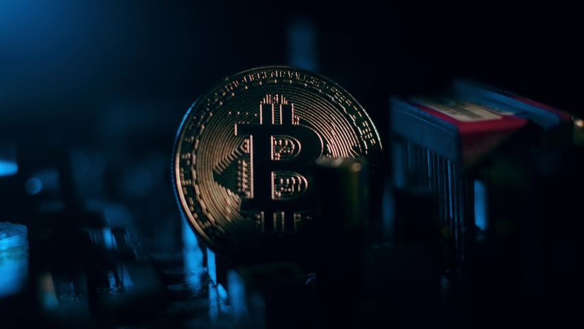 Golden Bitcoin Cryptocurrency on a computer board. Macro shooting. The concept of cryptocurrency with coins, bitcoin on a computer processor. New cryptocurrency, Bitcoin and computer duties. | Shutterstock HD Video #1044175213