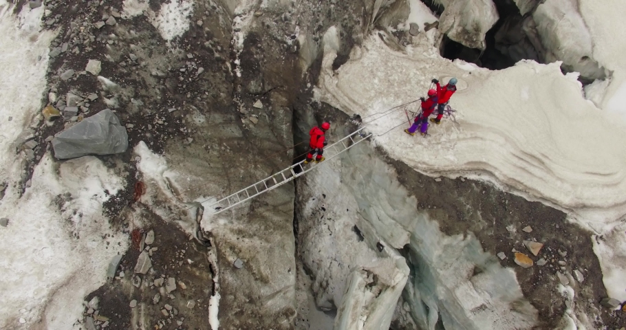 Himalayan mountaineers at Himalayas, upper Himalayan Range, Uttarakhand crossing ice mountains peaks (ice Craft) through ladder support. Experienced mountaineers.Professional mountaineers at Himalaya  | Shutterstock HD Video #1044315493