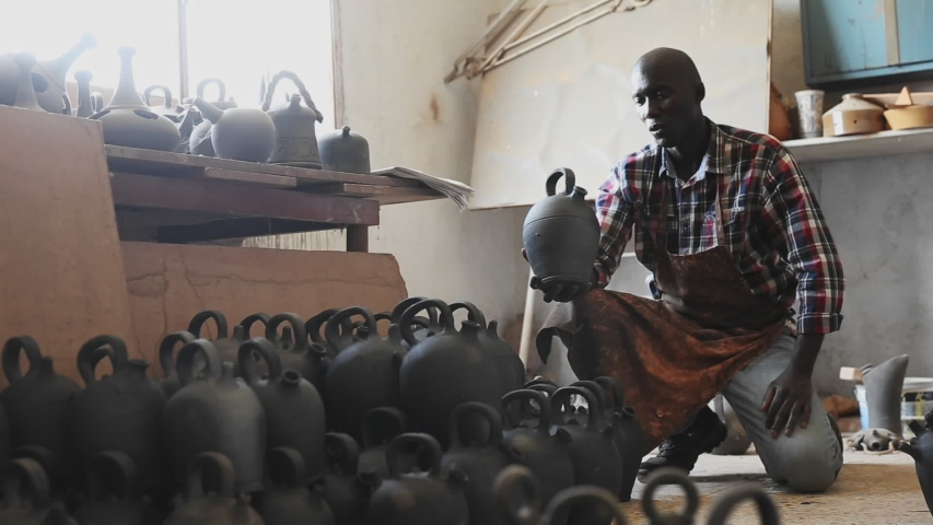 Positive African potter at work in pottery workshop, carrying ceramic products | Shutterstock HD Video #1044438673