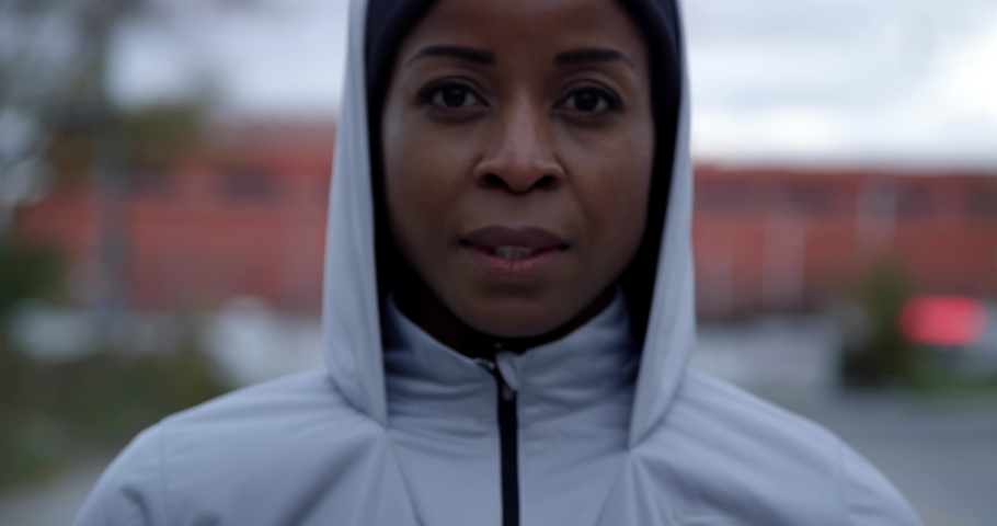 Close up portrait of jogger putting on hood and looking determined into camera, medium close #1044535783