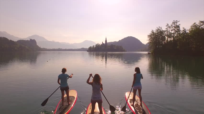 AERIAL: Girls SUP paddling towards the island in the middle of the lake at sunrise