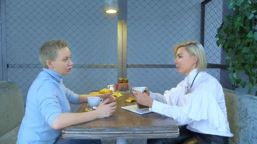 Two beautiful stylish women blondes communicate sitting in a cafe.   Shutterstock HD Video #1044817363