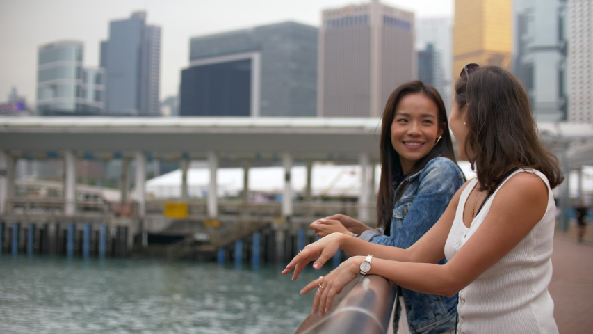 Two Young Women Friends Hang out by the Pier with Water and Buildings Around 4k    Shutterstock HD Video #1044832543