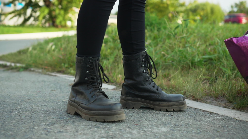 Female legs wearing black leather boots standing on asphalt road at summer girl in leather shoes walking on green grass in city park | Shutterstock HD Video #1044851383