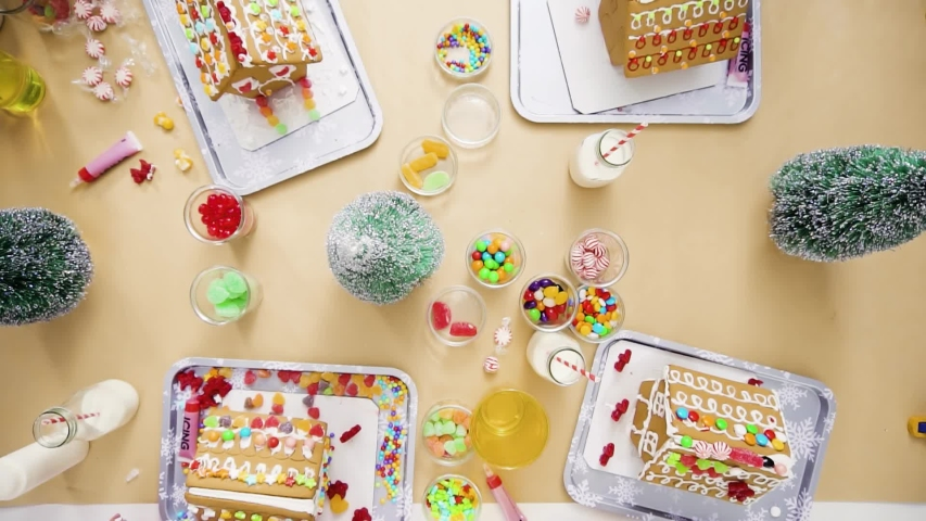 Flat lay. Step by step. Kids decorating small gingerbread houses at the Christmas craft party.   Shutterstock HD Video #1044886153