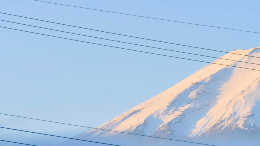 The electric post line in Kawaguchiko Japan and the white tip of the Mt. Fuji on the back | Shutterstock HD Video #1044891553