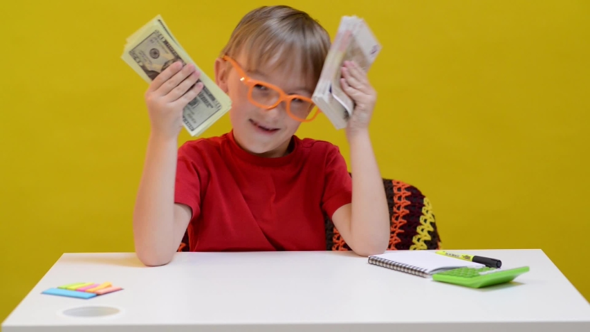 Clever little boy saving money and thinking where to invest money to get big income. Little business man planning new investment. Finance education and planning | Shutterstock HD Video #1044955273