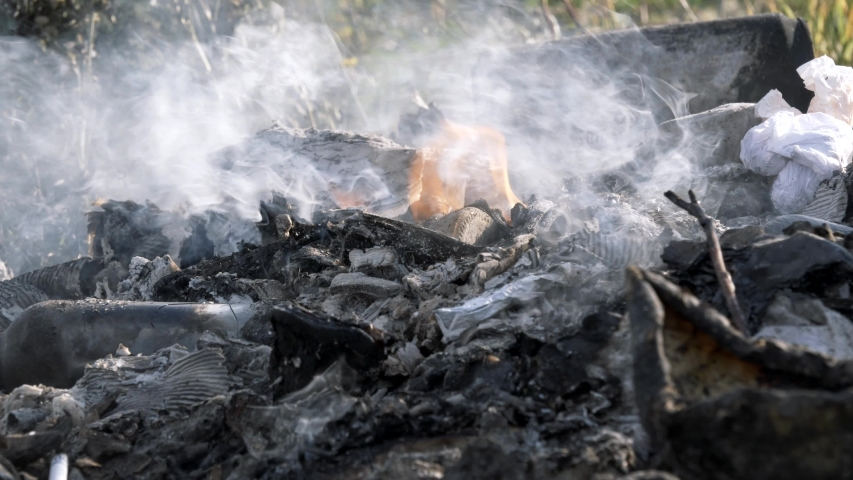 Bonfire. Garbage burning. People burn garbage in a fire, burn plastic bottles, glass bottles, paper, cardboard, plastic packaging. Environmental pollution and air pollution with toxic gases. | Shutterstock HD Video #1044994303