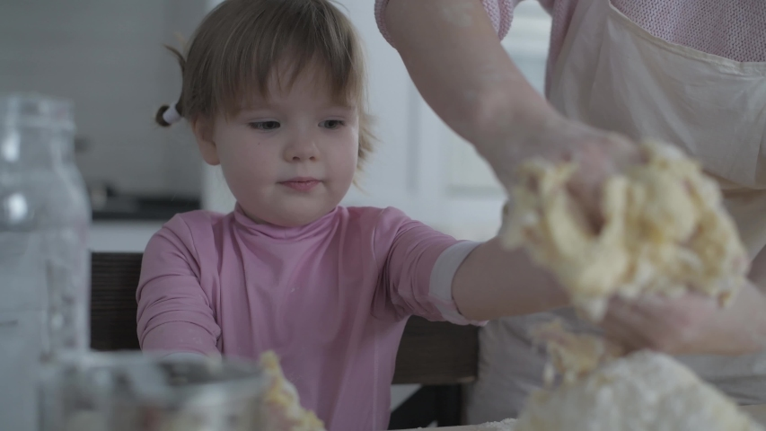 Mom teaches daughter to cook dough. Girl learns to cook pastries. Kneading the dough together. Roll out the dough for baking. Wonderful family in the spacious kitchen prepares food. Holiday cooking | Shutterstock HD Video #1045024303
