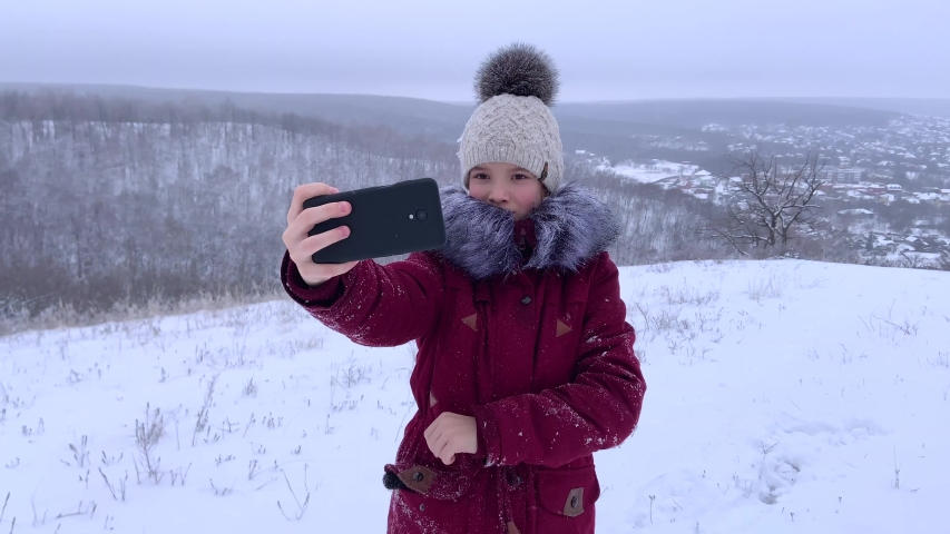 Teenager young caucasian girl taking selfie photos on smartphone and posing for a photo in the Russian winter snowy forest. Healthy open air spending holidays or weekend outdoors in cold weather. | Shutterstock HD Video #1045033363