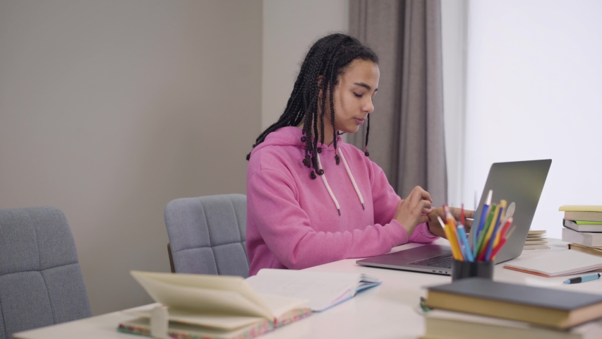 Side view of confident charming African American girl typing on laptop keyboard as her male groupmate coming. Young happy students talking and smiling. Intelligence, education, lifestyle. | Shutterstock HD Video #1045058383
