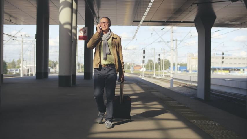 Portrait of elegant senior man walking on railway platform and dragging suitcase while talking on mobile phone. Aged businessman going on business trip by train | Shutterstock HD Video #1045059553
