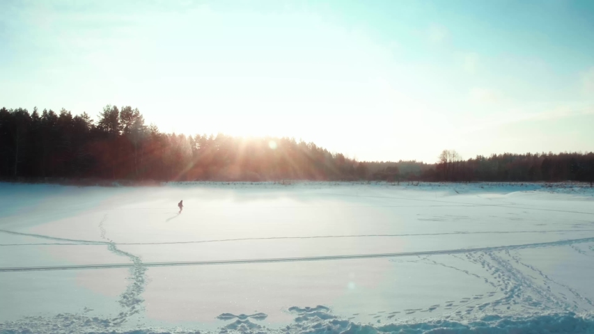 Silhouette of tourist jumping funny in a field in winter, raises arms into air | Shutterstock HD Video #1045080613