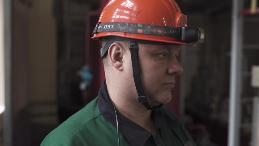 The face of a man in a work uniform of an engineer at work. The engineer speaks on the radio, puts on a helmet, glasses, and turns on a flashlight.  | Shutterstock HD Video #1045091563