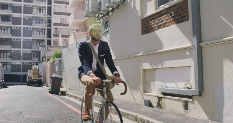 Front view of a young Caucasian businessman on the go in the city, riding a bike in the street, slow motion | Shutterstock HD Video #1045109653