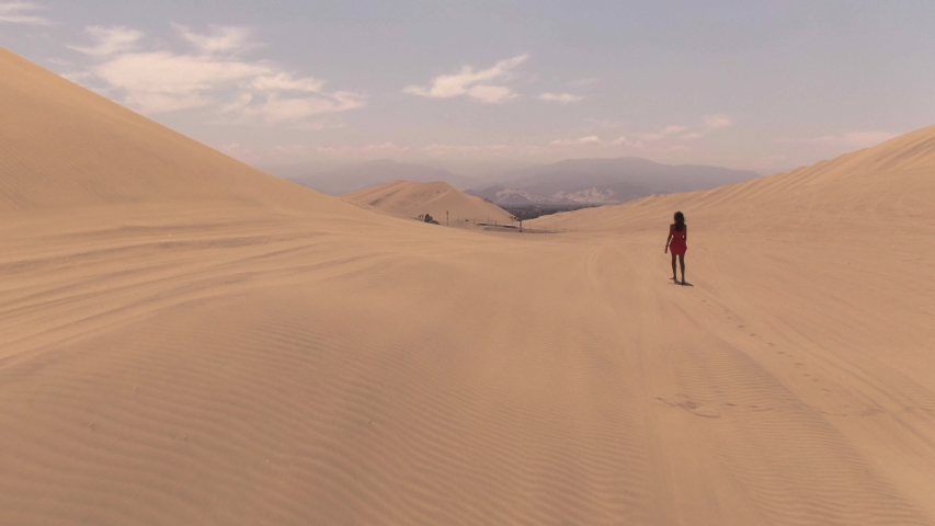 Sandy desert oasis lake. DRONE. Water in middle of hot sand desert. Romantic, holiday, couple, honeymoon, scenic shot, with sand and footprints. Tourism shot in Huacachina, Peru. Epic, dramatic shot. | Shutterstock HD Video #1045192783