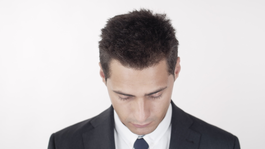 Close up of cheerful mixed-race man wearing elegant suit rising his head and looking at camera on white background | Shutterstock HD Video #1045209313