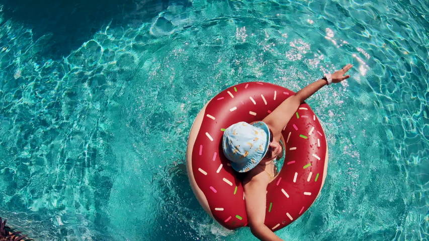 Top view of a lady spinning in a floating ring in the swimming pool | Shutterstock HD Video #1045232563