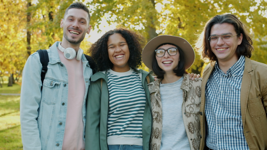 Slow motion of joyful youth men and women laughing outdoors on autumn day standing together and looking at camera, Happiness and friendship concept. | Shutterstock HD Video #1045402093