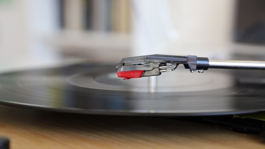 Disc turning on a turntable while the stylus lowers on it   Shutterstock HD Video #1045417003