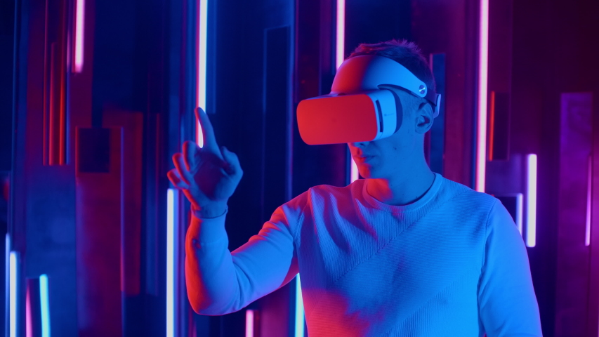 Faceless man wearing VR headset in dark space with neon light lamps, user turning head side to side looking virtual reality, shoting through colored flares and bokeh on foreground.   Shutterstock HD Video #1045442563