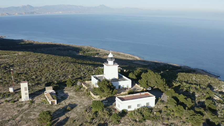 Aerial view of the Cabo Santapola lighthouse close to the cliffs of the cape and the Mediterranean Sea, in Spain. | Shutterstock HD Video #1046342293