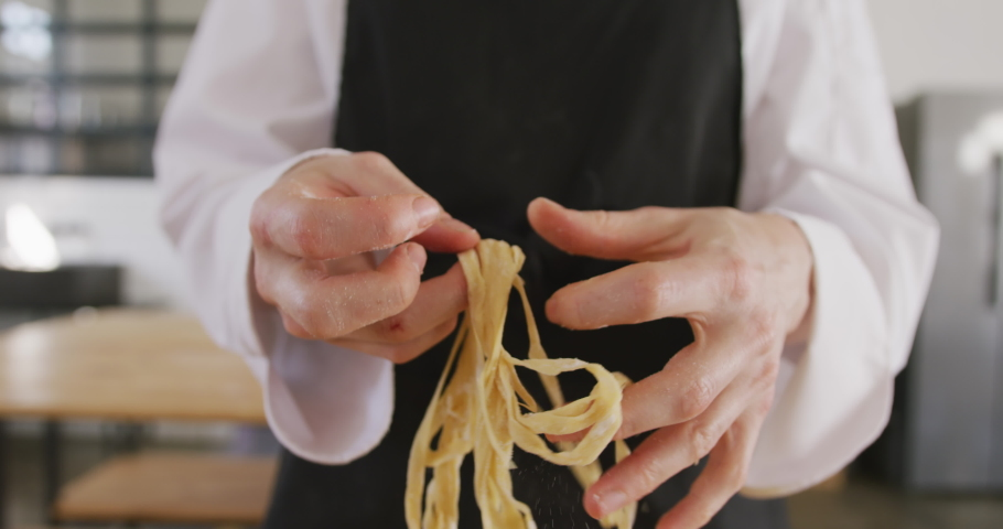 Front view mid section of the hands of a Caucasian female chef during a cookery class, separating sticky, fresh pasta, in slow motion | Shutterstock HD Video #1046542633