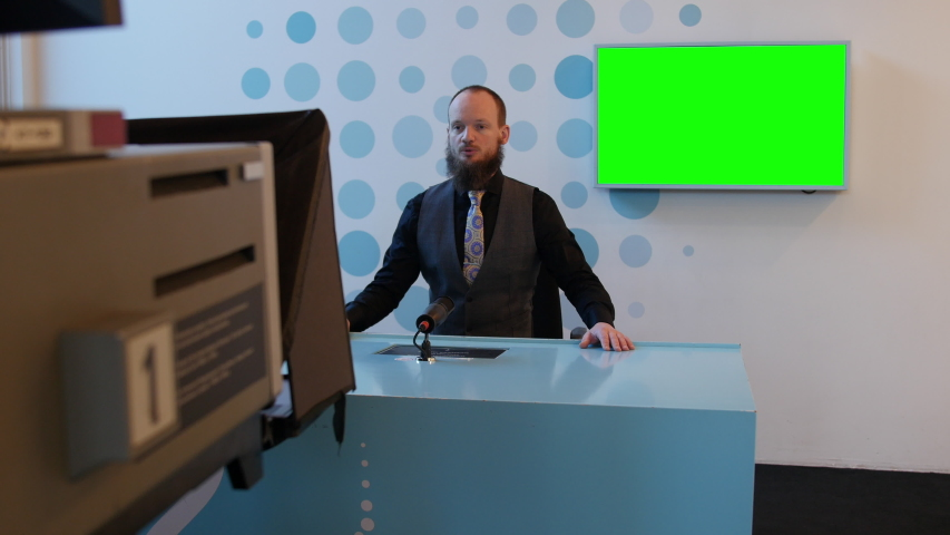 Handsome serious caucasian man adult with beard talking and interviewing on tv news event. broadcaster is sitting at a table and talking on a mock-up green screen in the background | Shutterstock HD Video #1046590723