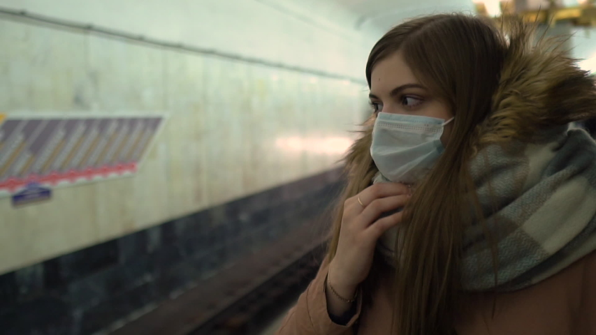 Ill woman  feeling sick, coughing, wearing protective mask against transmissible infectious diseases and as protection against the flu in public transport or subway. New coronavirus 2019-nCoV China  | Shutterstock HD Video #1046646493