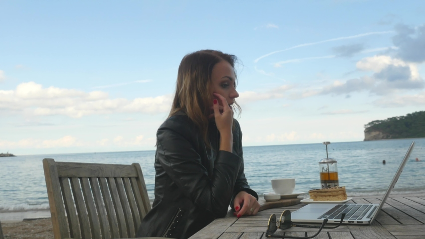 Worried business woman face looking at laptop. Working in outdoor cafe by the sea | Shutterstock HD Video #1046698213