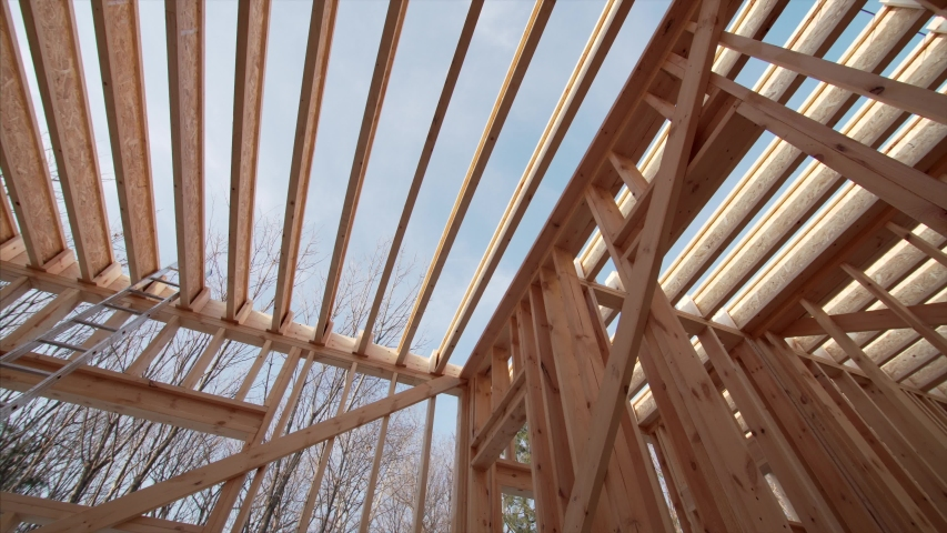 View from below of beams and trussings of a framed wooden house under construction   Shutterstock HD Video #1046725663
