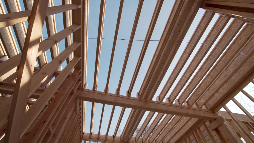 View from below of beams and trussings of a framed wooden house under construction. Blue sky is above   Shutterstock HD Video #1046725723