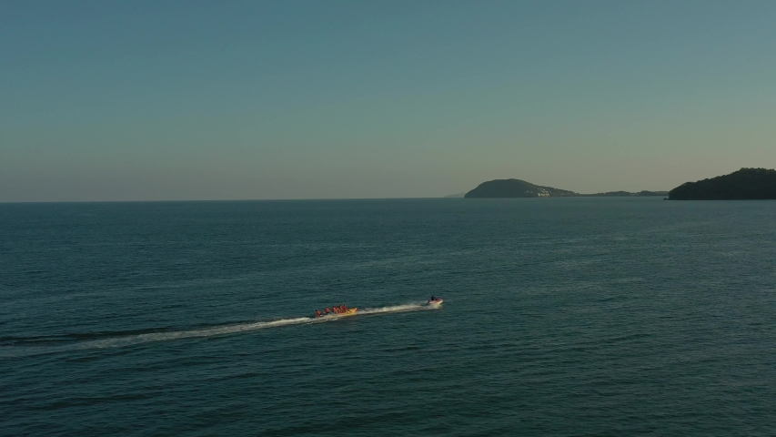 amazing view of moving fast speed boat on sea water close to islands in sunset and air banana with passengers and tourists on it below clear blue sky   Shutterstock HD Video #1046747263