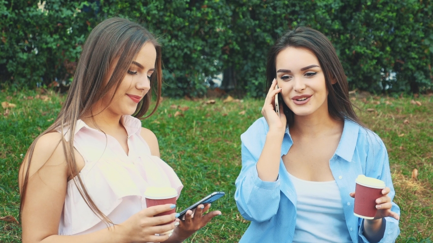 The girl after shopping sits in the park on the bench and one of the is on the phone, while another is sitting next to her. Close up. Copy space. 4K | Shutterstock HD Video #1046770933