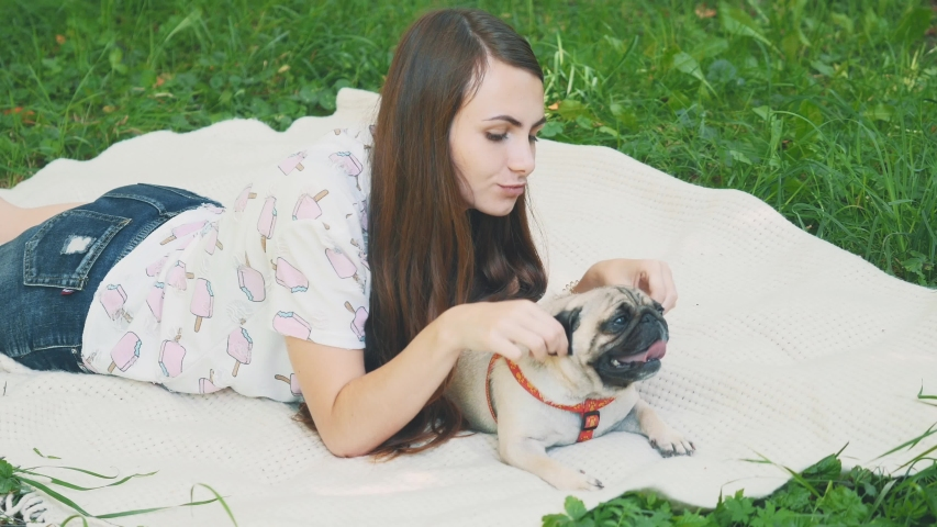 Smiling lady is taking free time with her dog. Woman relaxing in the nature with her little pug dog. Crop. Close up. Copy space. 4K. | Shutterstock HD Video #1046770993