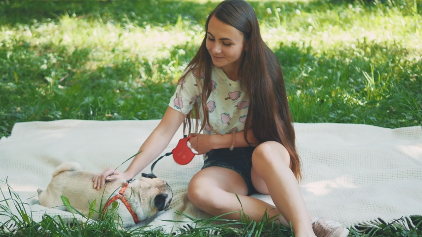 Smiling lady is taking free time with her dog. Woman relaxing in the nature with her little pug dog. Close up. Copy space. 4K. | Shutterstock HD Video #1046771113