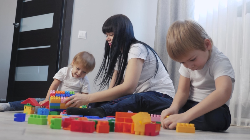 Childhood happy family mom and children are playing concept little girl and boy brother and sister collects constructor teamwork. child plays toys sitting floor. children play in team toys on floor | Shutterstock HD Video #1046814883