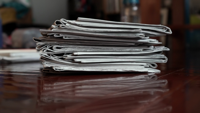 A pile of newspaper moving into the middle of frame by hand | Shutterstock HD Video #1046817073