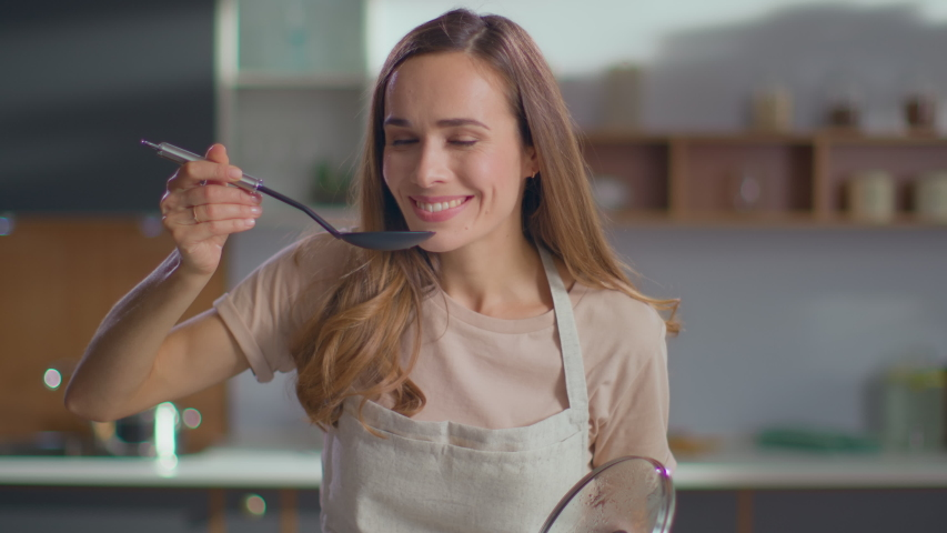 Pretty woman cooking soup on stove at kitchen. Close up of housewife preparing dinner at home. Young woman tasting soup on spoon at modern kitchen in slow motion | Shutterstock HD Video #1046849713