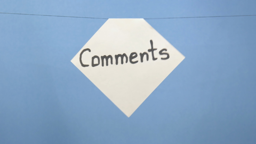 """Burning and smoking white sheet of paper with a black inscription """"comments"""" on a blue background 