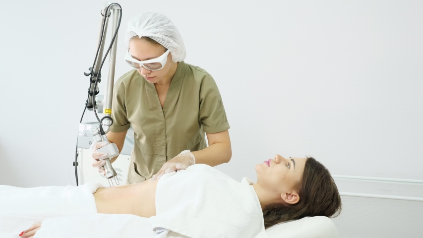 Professional therapist makes laser hair removal procedure on attractive lady belly in medical beauty clinic closeup | Shutterstock HD Video #1046890213