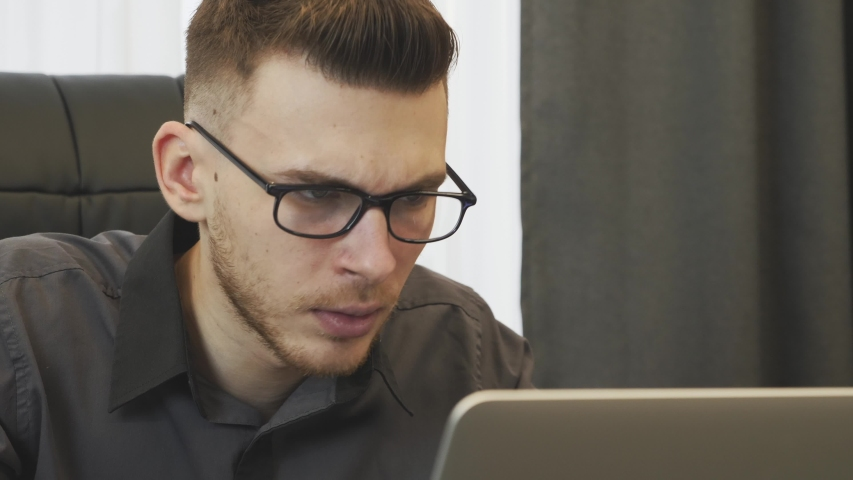 Close up of man shocked with news seen on internet. Businessman in glasses reading bad reviews of company on laptop screen. Male looking at computer screen and upset with financial company report | Shutterstock HD Video #1046891593