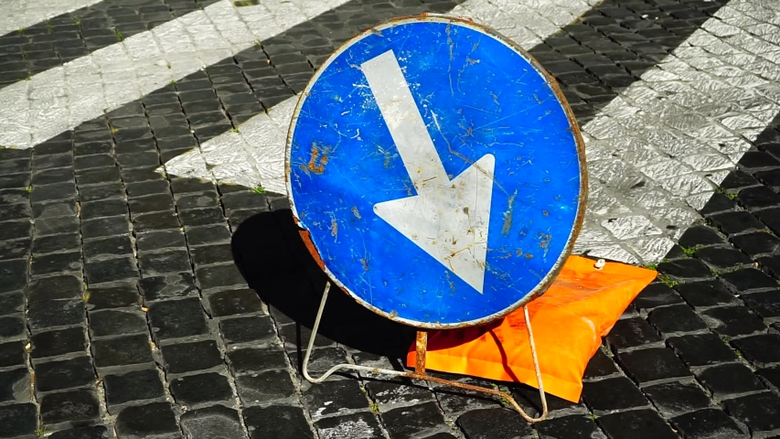 Metal sign blue background of forced passage to the right on a stone road with geometric design and pedestrian crossings | Shutterstock HD Video #1046924893
