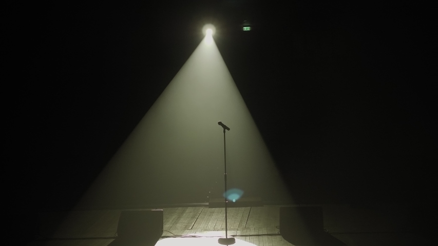 Close-up of microphone on stage against a black background with white lighting and smoke. The silhouette of the microphone in the dark. Music instrument concept. | Shutterstock HD Video #1046972353